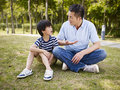 Asian father and son having a conversation elementary age sitting on grass outdoors serious Stock Photos