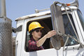 Asian female industrial worker adjusting mirror while sitting in logging truck Royalty Free Stock Photos