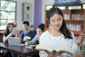 Asian female students holding for selection Book  in library Royalty Free Stock Photo