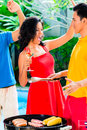 Asian friends celebrating pool party bbq with music wine and barbecue or Stock Image