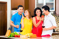 Asian friends cooking for dinner party cutting vegetables together in domestic kitchen drinking wine Stock Image