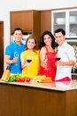 Asian friends cooking for dinner party cutting vegetables together in domestic kitchen drinking wine Royalty Free Stock Image