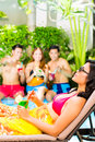 Asian friends partying at pool party in resort and drinking fancy cocktails hotel or club Stock Images