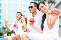 Asian friends sitting by hotel swimming pool couples drinking cocktails at Royalty Free Stock Image