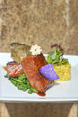 Asian fusion salmon rice and edible flowers glazed teriyaki with crisped skin on spinach with orange Royalty Free Stock Photos
