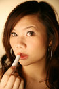 Asian girl applying lipstick Royalty Free Stock Photo