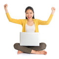 Asian girl arms up using laptop computer full body woman in yellow blouse excited when notebook seated on floor isolated on white Royalty Free Stock Photo