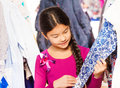 Asian girl with braid choosing and looking at item small the standing between clothes on the hangers in the shop Royalty Free Stock Images