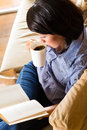 Asian girl with cup reading book student young woman or sitting on a sofa a of coffee a she is learning Stock Images