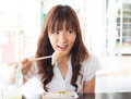 Asian girl eating dim sum rice noodle roll chee cheong fun at restaurant young breakfast cantonese cuisine using chopsticks Stock Image
