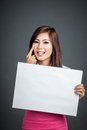 Asian girl hold blank sign sticking out her tongue on gray background Stock Photography