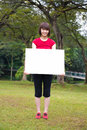 Asian girl holding a placard outdoor happy white blank card at park Royalty Free Stock Images