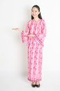 Asian girl in pink batik dress showing somethings full body portrait of happy southeast woman hands something standing on plain Stock Photos