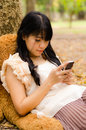 Asian girl playing cell phone Stock Image