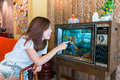 An Asian girl is playing with the goldfish in the tv fish tank Royalty Free Stock Photo