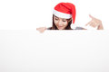 Asian girl with red santa hat look down and point to a blank si sign isolated on white background Stock Photos