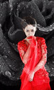 Asian girl in a red transparent dress sitting on the floor and shoes with black hair the studio Royalty Free Stock Photo
