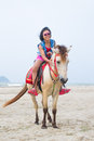 Asian girl riding horse on the beach Stock Photo