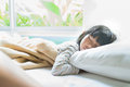 Asian girl sleeping on bed covered with blanket in room Royalty Free Stock Photos