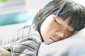 Asian girl sleeping on bed covered with blanket in room Stock Image