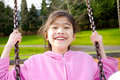 Asian girl smiling on a swing at the park Royalty Free Stock Photo