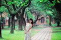 A asian girl stroll in the park park,filled with smile enjoy trees and classical architecture Royalty Free Stock Photography