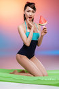 Asian girl in swimsuit kneeling on swimming mattress and holding watermelon slice on stick Royalty Free Stock Photo