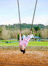 Asian girl swinging upside down at park Stock Photography