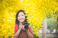 Asian girl take photo with blooming yellow flower Royalty Free Stock Photo