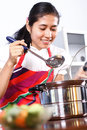 Asian girl tasting her cooking woman Royalty Free Stock Photos