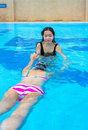An asian girl is teaching another to swim in the swimming pool Royalty Free Stock Photography