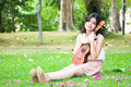 Asian girl with ukulele guitar outdoor in garden Royalty Free Stock Photos