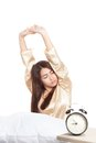 Asian girl  wake up and stretching with alarm clock Royalty Free Stock Photo