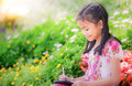 Asian girl write an note pad in the flower park for play a tablet game Stock Image