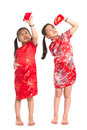 Asian girls peeking into red packet happy during chinese new year with traditional cheongsam full length standing isolated on Royalty Free Stock Photo