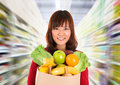 Asian grocery shopping smiling young woman holding paper bag full of groceries in a store supermarket Stock Photography