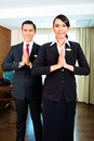 Asian hotel staff greeting with hands put together portrait of Stock Photo