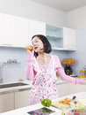 Asian housewife in kitchen singing using carrot as microphone Stock Photography