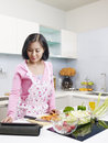 Asian housewife looking at tablet computer while preparing meal Royalty Free Stock Image