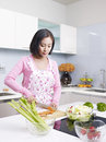 Asian housewife young woman making salad in kitchen Royalty Free Stock Images