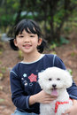 Asian kid playing with dog Royalty Free Stock Photos