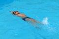 Asian kid swims in swimming pool - back stroke kick style Royalty Free Stock Photo