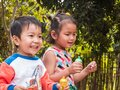 Asian kids boy and girl playing bubbles together outdoor in nature countryside garden background.