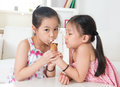 Asian kids eating ice cream cone children sharing an at home beautiful girls model Royalty Free Stock Photos