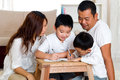 Asian kids writing parents monitoring their doing homework Stock Images