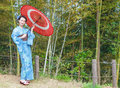 Asian kimono woman with bamboo grove japanese red traditional umbrella Stock Photography