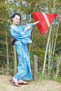 Asian kimono woman with bamboo grove japanese red traditional umbrella Royalty Free Stock Photo