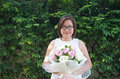 Asian lady wearing glasses smiling and holding beautiful bouque bouquet on her hands with green leaves background Royalty Free Stock Photos