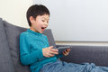 Asian little boy feel exciting for using tablet and sitting on sofa Royalty Free Stock Photography