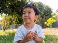 Asian little child boy holding glass of orange juice with smiling Royalty Free Stock Photo